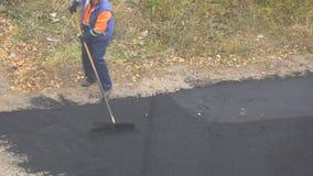 Trabalhador fêmea durante a estrada asfaltada Trabalho manual fêmea pesado na construção video estoque