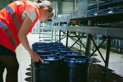 Trabalhador fêmea na fábrica da cerveja mulher do retrato na veste, estando na linha produção alimentar do fundo, controle de ges Fotografia de Stock
