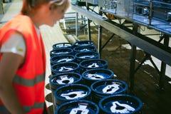 Trabalhador fêmea na fábrica da cerveja mulher do retrato na veste, estando na linha produção alimentar do fundo, controle de ges Imagens de Stock