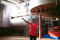 Trabalhador fêmea na fábrica da cerveja mulher do retrato na veste, estando na linha produção alimentar do fundo, controle de ges Imagens de Stock Royalty Free