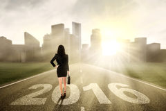 Trabalhador fêmea que anda na estrada com números 2016 Imagens de Stock Royalty Free
