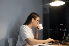 Trabalhador fêmea que come o café ao trabalhar tarde imagens de stock royalty free