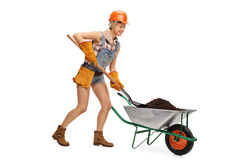 Trabalhador fêmea que descarrega um carrinho de mão Fotos de Stock Royalty Free