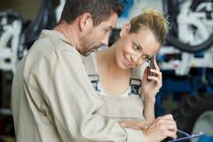 Trabalhador fêmea que fala no smartphone ao olhar a prancheta dos colegas imagens de stock royalty free