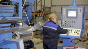 Trabalhador fêmea que opera o painel de controle industrial, exposição em um equipamento industrial moderno filme