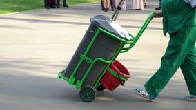 Trabalhador fêmea superior do jardim no escaninho de lixo de rolamento uniforme nas rodas no parque da cidade filme