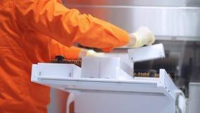 Trabalhador farmacêutico que carrega tubos de ensaio médicos na máquina de empacotamento farmacêutico filme