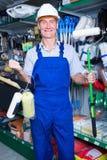 Trabalhador feliz no rolo de pintura de compra do capacete de segurança Imagens de Stock Royalty Free