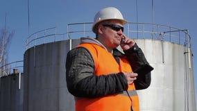 Trabalhador feliz que fala no telefone celular perto do tanque de óleo video estoque