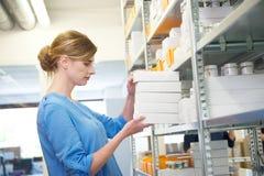 Trabalhador fêmea novo que guardara caixas no armazém Imagem de Stock Royalty Free