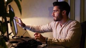 Trabalhador home que senta-se na mesa usando o computador do écran sensível video estoque