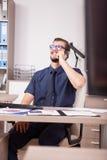 Trabalhador incorporado de sorriso na camisa azul e laço que falam no pH Foto de Stock Royalty Free