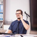 Trabalhador incorporado de sorriso na camisa azul e laço que falam no pH Imagem de Stock Royalty Free