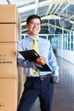 Trabalhador indonésio novo no armazém com varredor Imagem de Stock Royalty Free
