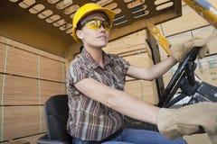 Trabalhador industrial fêmea que conduz o caminhão de empilhadeira com as pranchas de madeira empilhadas no fundo Fotos de Stock