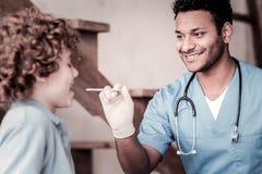 Trabalhador médico ocupado positivo que verifica a garganta da criança imagens de stock