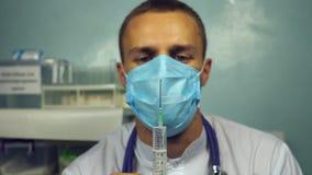 Trabalhador médico que prepara a seringa para a injeção Retrato do doutor caucasiano masculino novo na máscara que derrama um líq filme