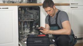 Trabalhador manual com o PC da tabuleta que repara a máquina de lavar louça doméstica video estoque