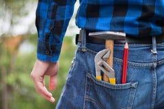 Trabalhador manual da casa: Opinião traseira um homem novo com martelo, lápis e prendedor em seu bolso foto de stock