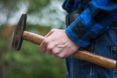 Trabalhador manual da casa: Opinião traseira um homem novo com o martelo em sua mão fotografia de stock royalty free