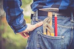 Trabalhador manual da casa: Opini?o traseira um homem novo com martelo, l?pis e prendedor em seu bolso fotografia de stock