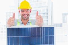 Trabalhador manual de sorriso com painel solar que gesticula os polegares acima fotografia de stock