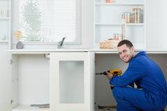 Trabalhador manual de sorriso que repara uma porta fotografia de stock royalty free