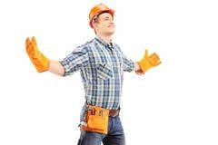 Trabalhador manual feliz com os braços de espalhamento do capacete Fotografia de Stock Royalty Free