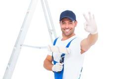Trabalhador manual feliz com rolo de pintura que gesticula está bem Fotos de Stock Royalty Free