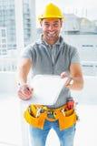 Trabalhador manual feliz que dá a prancheta para a assinatura Imagens de Stock