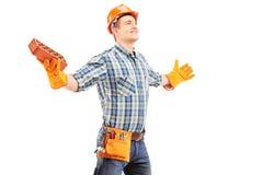 Trabalhador manual feliz que guardara um tijolo e que espalha os braços Imagem de Stock Royalty Free