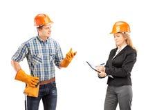 Trabalhador manual masculino que tem uma conversação com arquiteto fêmea imagem de stock royalty free