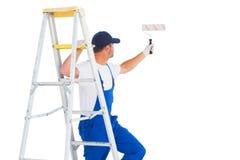 Trabalhador manual na escada ao usar o rolo de pintura Imagens de Stock
