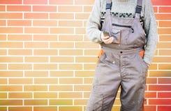 Trabalhador manual anônimo com telefone celular Imagem de Stock