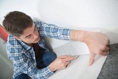 Trabalhador manual novo que instala o tapete com cortador imagens de stock