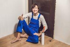Trabalhador manual novo que instala a porta com uma espuma da montagem em uma sala fotografia de stock royalty free