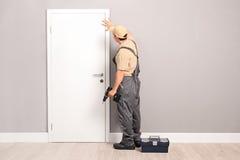 Trabalhador manual novo que instala uma porta Imagem de Stock Royalty Free