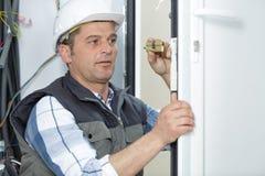 Trabalhador manual que cabe a porta nova imagem de stock