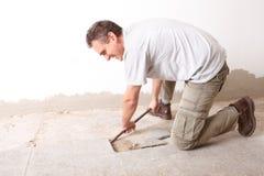 Trabalhador manual que desmonta telhas de assoalho velhas Fotografia de Stock Royalty Free
