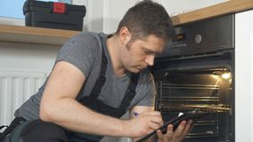 Trabalhador manual que faz a inspeção do forno doméstico video estoque