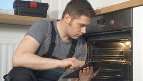 Trabalhador manual que faz a inspeção do forno doméstico filme