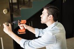 Trabalhador manual que fixa um botão de porta foto de stock