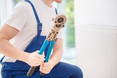 Trabalhador manual que guarda a chave hidráulica imagem de stock