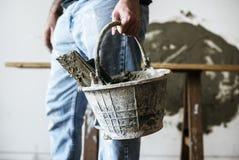 Trabalhador manual que guarda o cimento da cesta para a construção fotos de stock royalty free