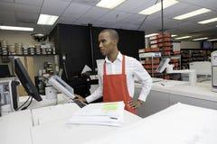 Trabalhador manual que olha a máquina da caixa registadora foto de stock