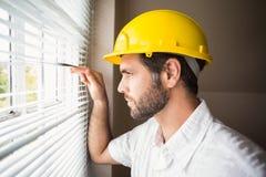 Trabalhador manual que olha para fora a janela Fotos de Stock