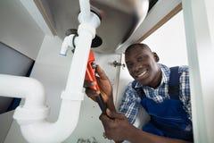 Trabalhador manual que repara a tubulação do dissipador Fotos de Stock