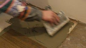 Trabalhador manual Spreading Glue On o assoalho vídeos de arquivo