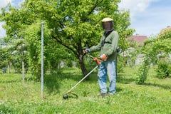 Trabalhador masculino com o ajustador mo do gramado da corda da ferramenta elétrica Foto de Stock Royalty Free