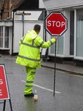 Trabalhador masculino da estrada com o revestimento amarelo e a calças fluorescentes que guardam o sinal vermelho da parada imagens de stock royalty free